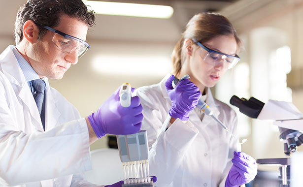 Two lab technicians working with a pipette